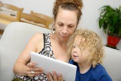 Ребенок и ее мама используют таблетку Стоковые Изображения RF
