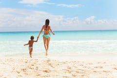 Ребенок и женщина бежать к морю держа руки Стоковая Фотография