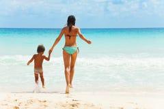 Ребенок и женщина держа руки на предпосылке моря Стоковое Изображение