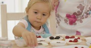 Ребенок и женщина подготавливая булочки на таблице Стоковое Изображение RF