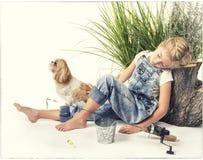Ребенок или маленькая девочка при ее собака принимая ворсину или спать пока Стоковые Изображения RF