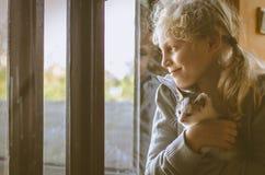 Ребенок и кот самостоятельно окном стоковое фото rf