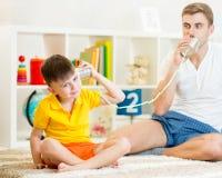 Ребенок и отец имея телефонный звонок с жестяными коробками Стоковая Фотография