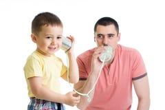 Ребенок и папа имея телефонный звонок с жестяными коробками стоковое изображение rf