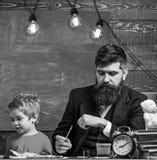 Ребенок и учитель на занятых сторонах красить, рисуя Учитель с бородой, отец и маленький сын в классе пока рисующ стоковые изображения