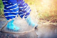 Ребенок идя в wellies в лужице на ненастной погоде Стоковые Фото