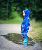 Ребенок идя в wellies в лужице на ненастной погоде Стоковые Изображения RF