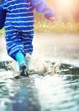 Ребенок идя в wellies в лужице на ненастной погоде Стоковое Изображение