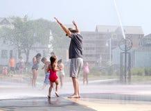 Ребенок и grandpa играя на фонтанах водоворота Стоковые Изображения RF