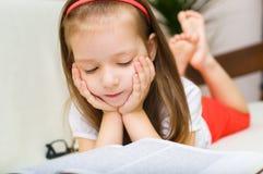 Ребенок книга чтения пока лежащ на кресле стоковая фотография rf