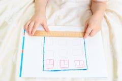 Ребенок конструируя и измеряя дом Стоковые Изображения RF
