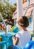Ребенок контролирует машину Езды на привлекательностях Парк атракционов темы Gardaland в Castelnuovo Del Garda, Вероне, Италии Стоковая Фотография RF