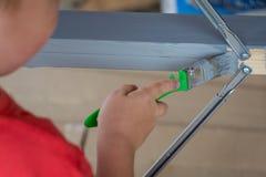 Ребенок красит деревянный продукт с tassel Работа и трудолюбие стоковые изображения rf