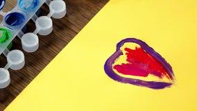Ребенок крася изображение Маленькие girl's вручают красить красочное сердце сток-видео