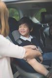 Ребенок крепления женщины с ремнем безопасности безопасности в автомобиле Стоковая Фотография RF