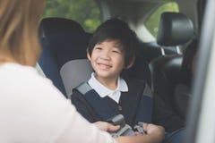 Ребенок крепления женщины с ремнем безопасности безопасности в автомобиле Стоковые Изображения