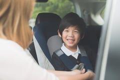 Ребенок крепления женщины с ремнем безопасности безопасности в автомобиле Стоковые Фотографии RF
