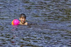 Ребенок купает в озере с мальчиком шарика плавает в озере в лете стоковое изображение