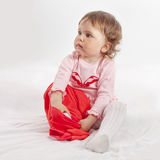 Ребенок кладет красные брюки дальше стоковая фотография