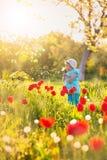 Ребенок маленькой девочки в поле с зеленой травой и зацветая тюльпаном стоковое изображение rf