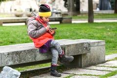 Ребенок маленькой девочки используя парк мобильного телефона публично Стоковые Фото