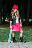 Ребенок маленькой девочки моды портрета стильный представляя с скейтбордом на парке города стоковые изображения rf