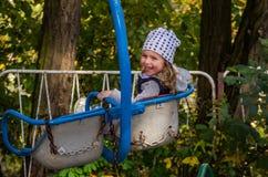Ребенок маленькой девочки отбрасывая на качании в парке атракционов Стоковое фото RF