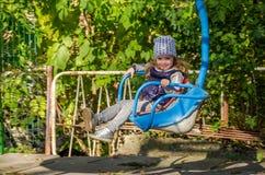 Ребенок маленькой девочки отбрасывая на качании в парке атракционов Стоковая Фотография RF