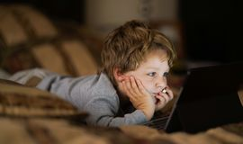 Ребенок малыша наблюдая таблетку Стоковые Изображения