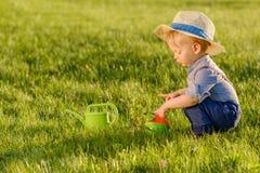 Ребенок малыша outdoors Одна соломенная шляпа годовалого ребёнка нося используя моча чонсервную банку стоковое изображение
