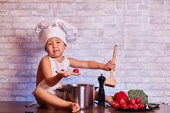 Ребенок, мальчик в рисберме, сидит на кухонном столе, в крышке повара, держит деревянные ложки и томат, рядом с ним a стоковые изображения