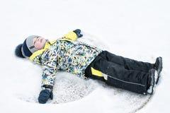 Ребенок, мальчик, лож на снеге, делает ангела снега с его оружиями и ногами, эмоциями, смехом Стоковые Фото