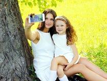 Ребенок матери и дочери принимая портрет selfie на smartphone outdoors стоковое фото rf