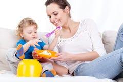 Ребенок матери подавая на софе Стоковое фото RF