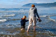 Ребенок матери рука об руку на пляже стоковая фотография rf