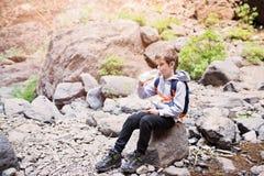 Ребенок мальчика выпивая разлитую по бутылкам минеральную воду на горной тропе Стоковое фото RF