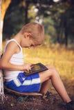 Ребенок мальчика играя с ПК таблетки внешним стоковая фотография rf