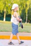 Ребенок мальчика идя с скейтбордом за взглядом внешним стоковая фотография