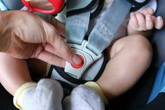Ребенок младенца сидя в автокресле с ремнем безопасности запертым Стоковые Изображения RF