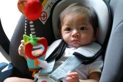 Ребенок младенца сидя в автокресле с ремнем безопасности запертым Стоковая Фотография RF