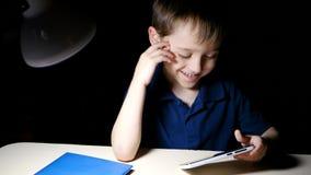 Ребенок наслаждается наблюдать мультфильм дома вечером используя смартфон и усмехаться сток-видео