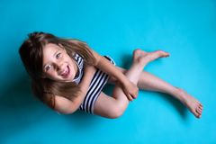 Ребенок на простой голубой предпосылке смотря сидеть камеры стоковые изображения rf