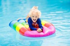 Ребенок на раздувном поплавке в бассейне Стоковые Изображения