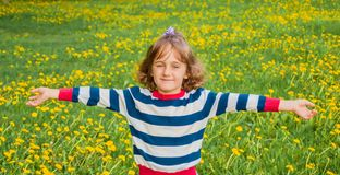 Ребенок на лужайке с одуванчиками Стоковые Изображения
