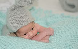 ребенок 4 недель старый newborn с серой шляпой на зеленом одеяле стоковое фото