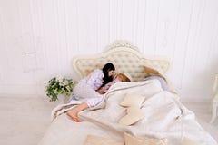 Ребенок не слушать только соединять пробовать спать, лежащ на кровати в whi стоковые фото