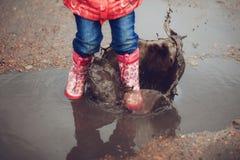 Ребенок нося розовые ботинки дождя скача в лужицу Стоковое фото RF