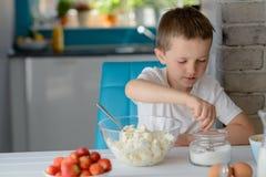 Ребенок добавляя сахар к творогу в шаре стоковые изображения rf