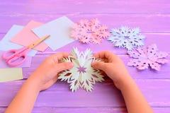 Ребенок отрезал снежинку покрашенной бумаги Маленький ребенок держит бумажную снежинку в руках Листы покрашенной бумаги, ножницы, Стоковая Фотография