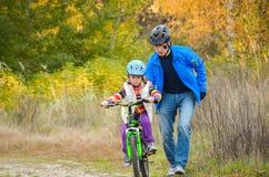 Ребенок отца уча для того чтобы ехать велосипед Стоковое фото RF